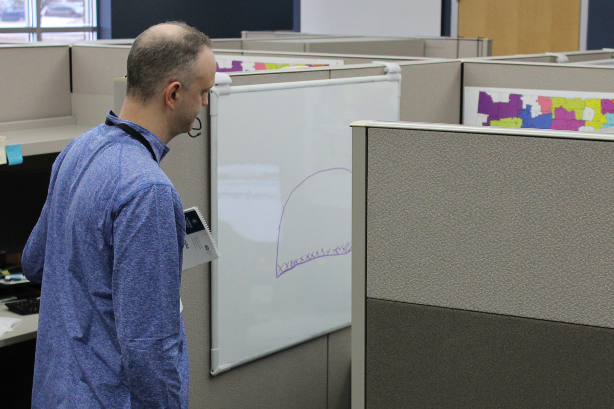 Chaplain talking with employee in cubicle