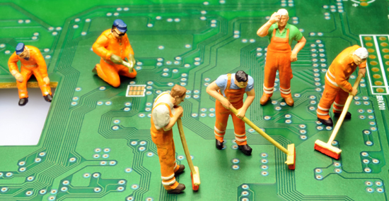 Little figurines cleaning a computer circuit board