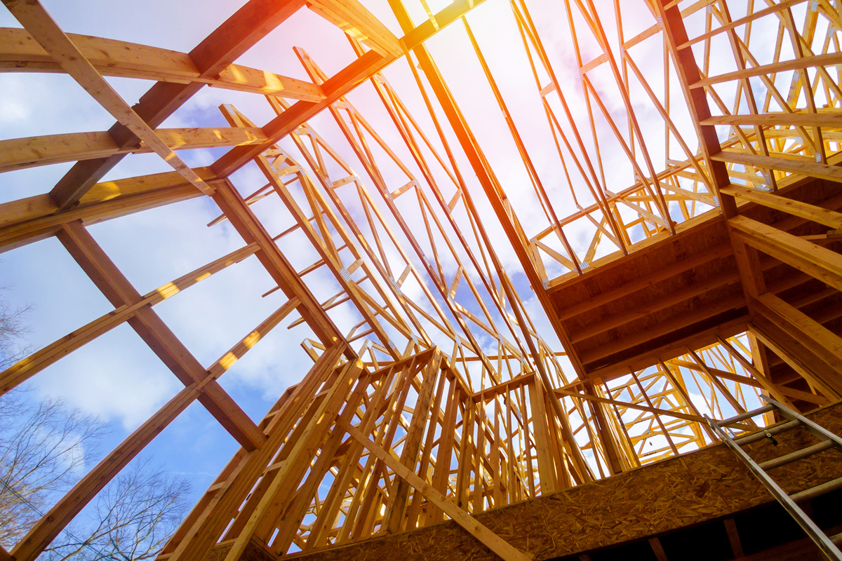 looking up to the sky through trusses of a new home being built