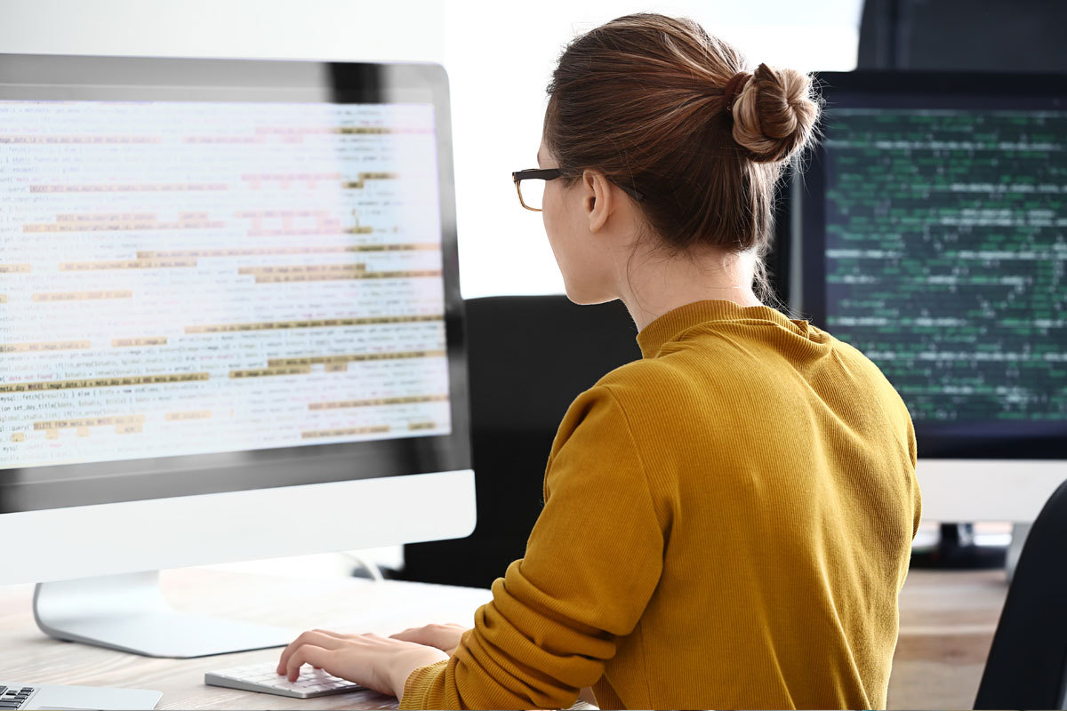 Woman looking at code on computer screen