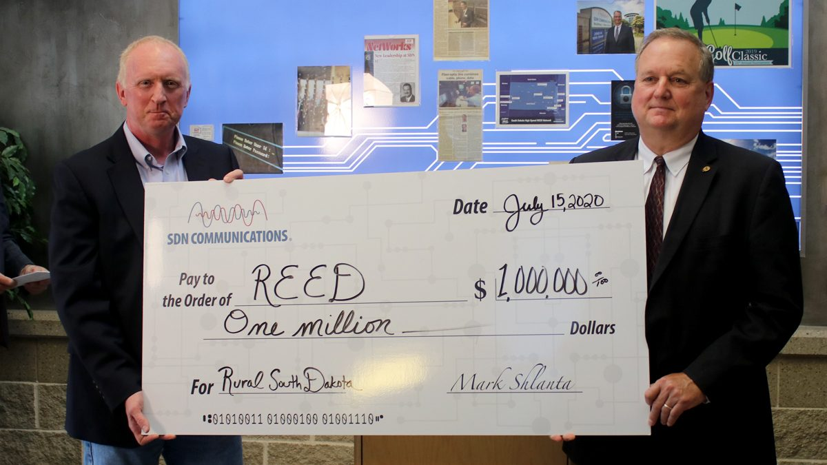 Check presentation of one million dollars by SDN board president Denny Law to East River Electric's Tom Boyko