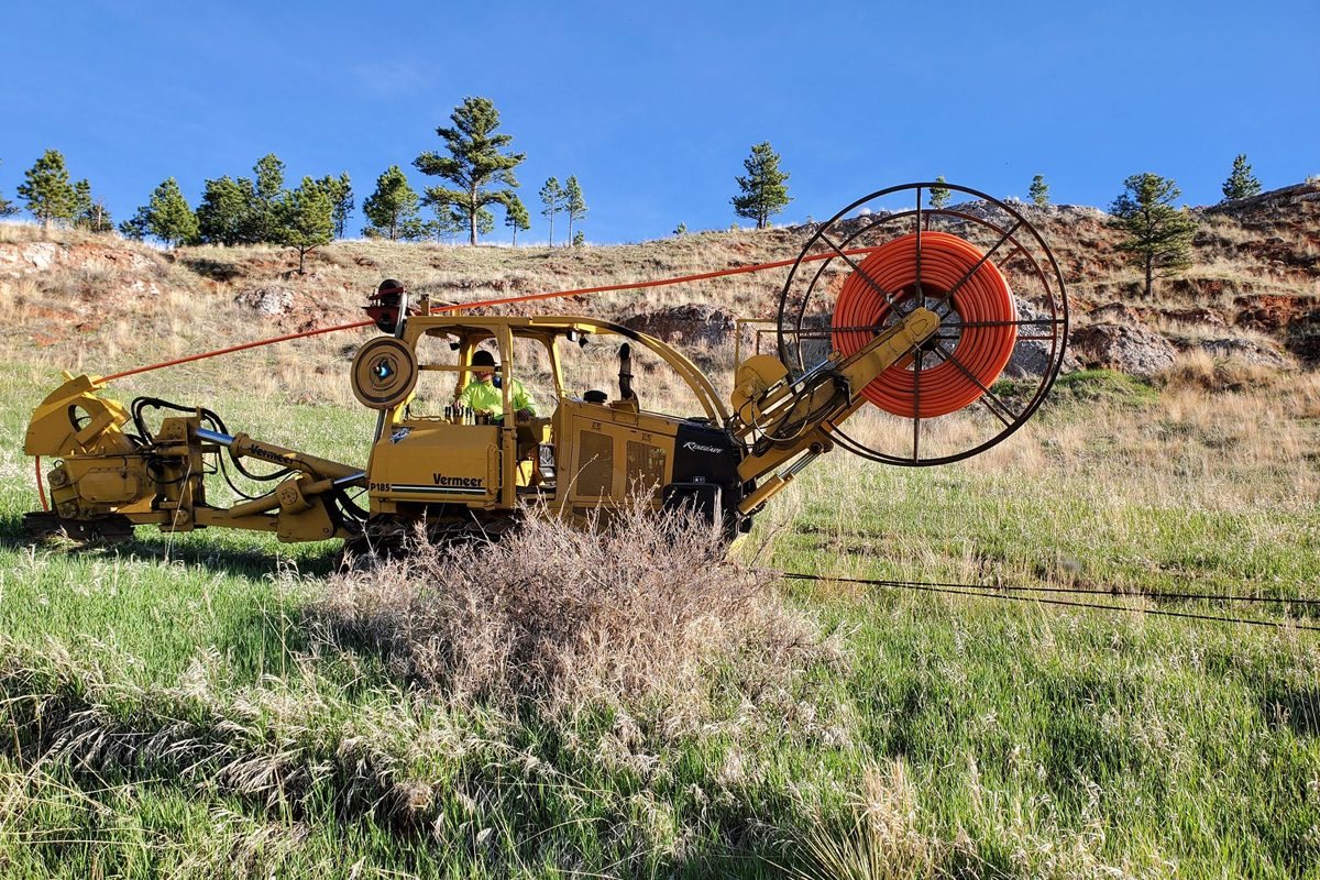 Large equipment installing fiber into the red rock of Rapid City